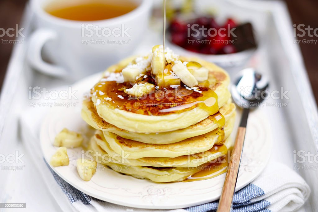 Banana pancakes with maple syrup stock photo