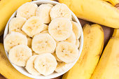 Banana slices into a bowl over a wooden table.