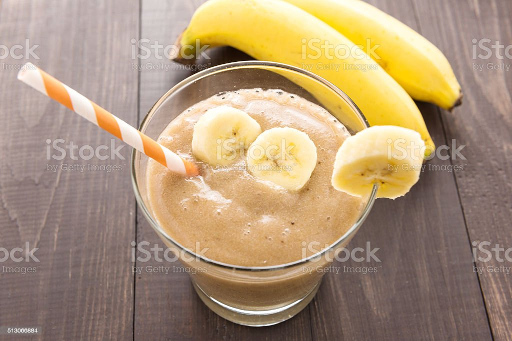 Banana smoothie and fresh banana on wooden table stock photo