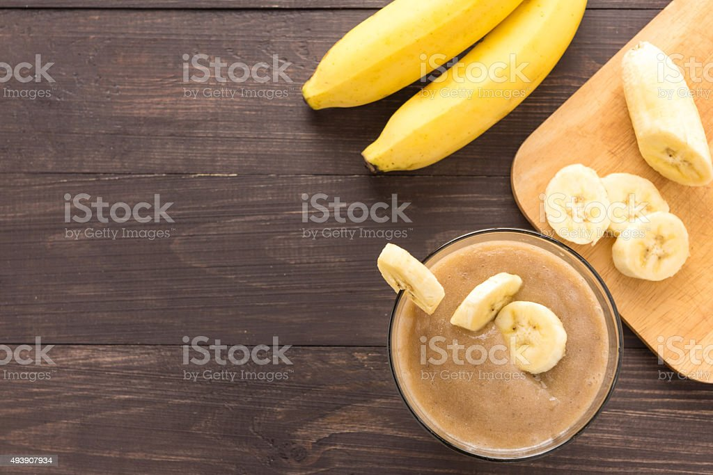 Banana smoothie on wooden background. Top view stock photo