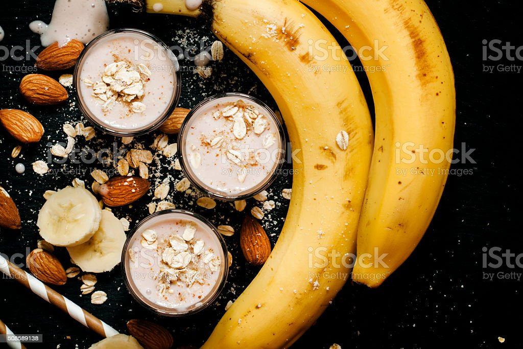 Banana smoothie with ground almonds and oat flakes stock photo
