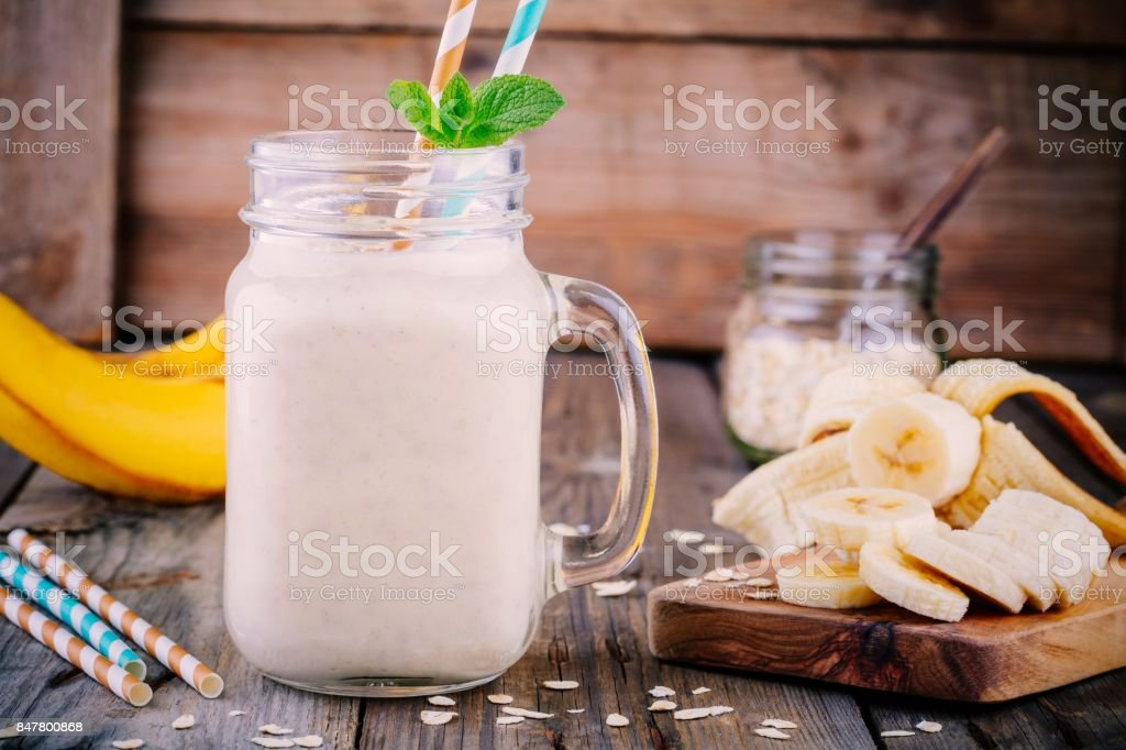 banana smoothie with oat flakes in mason jar on a wooden background stock photo