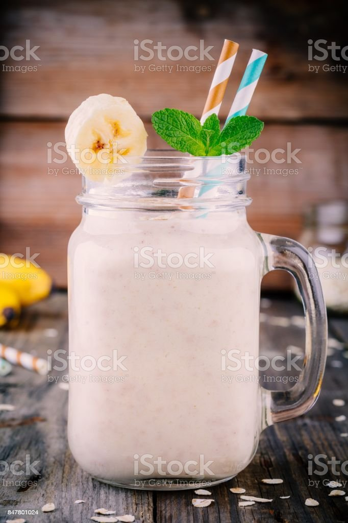 banana smoothie with oatmeal in mason jar on a wooden background stock photo