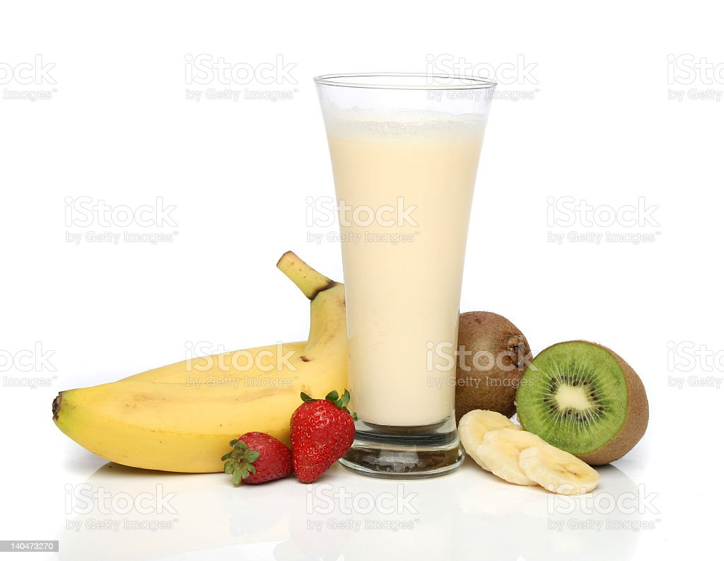 Banana, strawberry and kiwi next to glass of milkshake stock photo