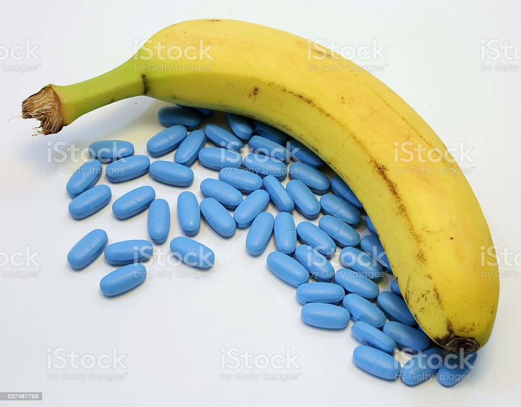 banana with many blue pills for male problems stock photo