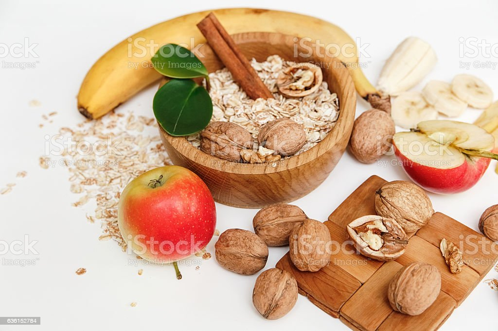 Banana,Apple,Orange,Walnuts,Wooden Plate.Rolled Oats,Wooden Spoon stock photo