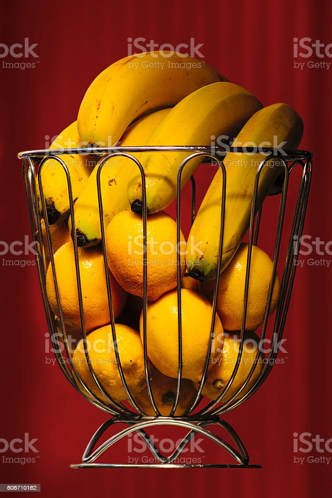 Bananas and oranges in iron basket and garnet curtain stock photo
