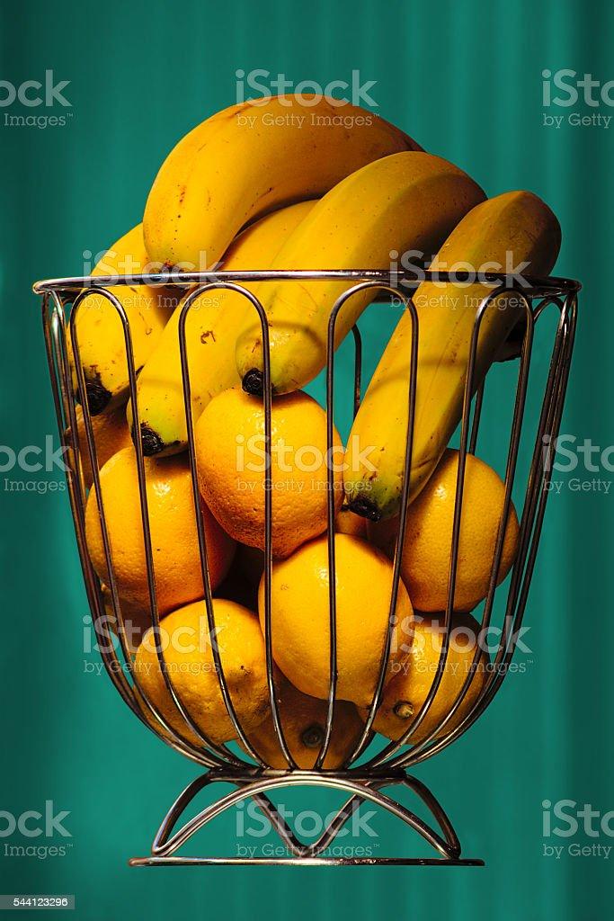 Bananas and oranges in iron basket stock photo