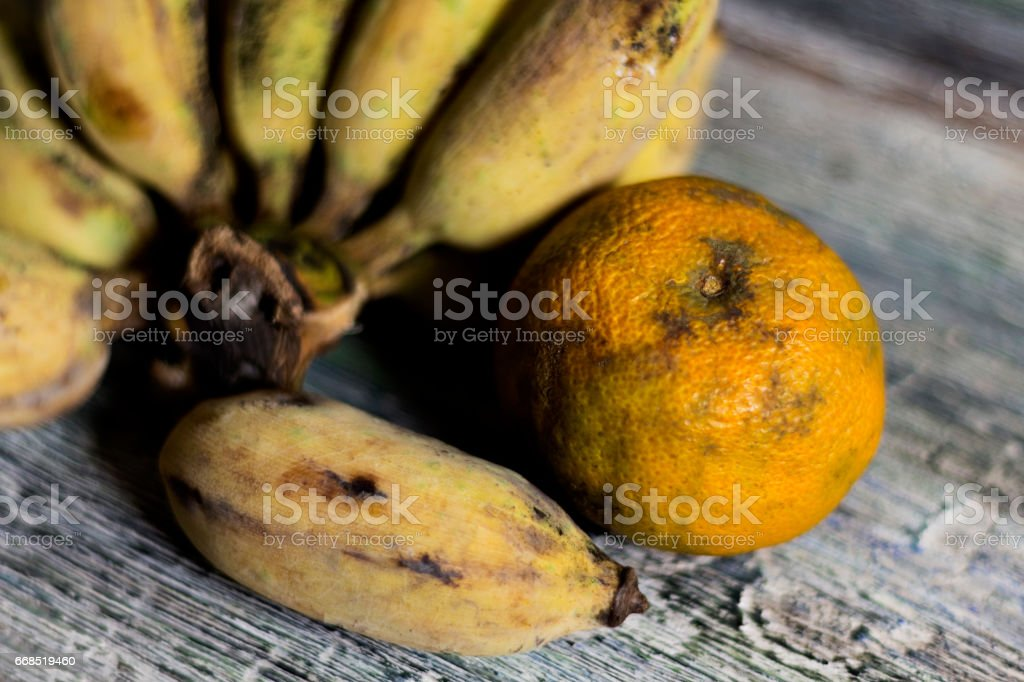 Bananas and oranges to wither on wood table stock photo