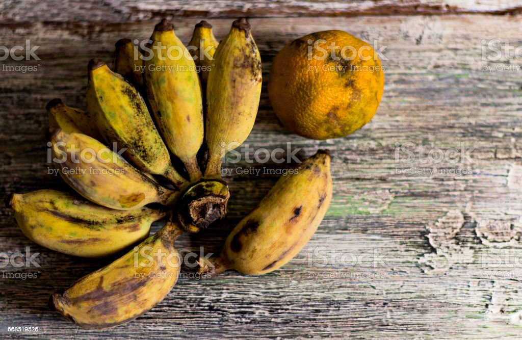 Bananas and oranges to wither on wood table. stock photo