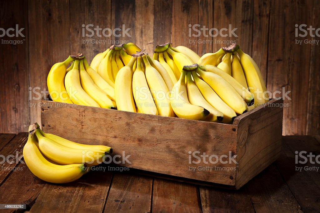 Bananas in a crate on rustic wood table stock photo