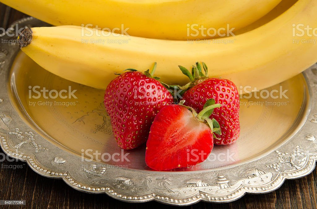 Bananas with strawberries on a vintage plate closeup stock photo