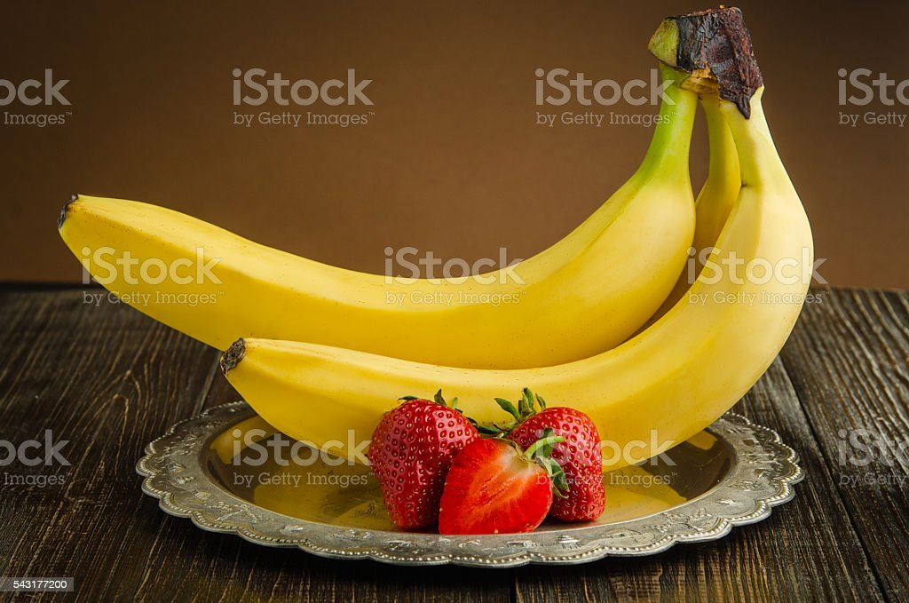 Bananas with strawberries on a vintage plate stock photo