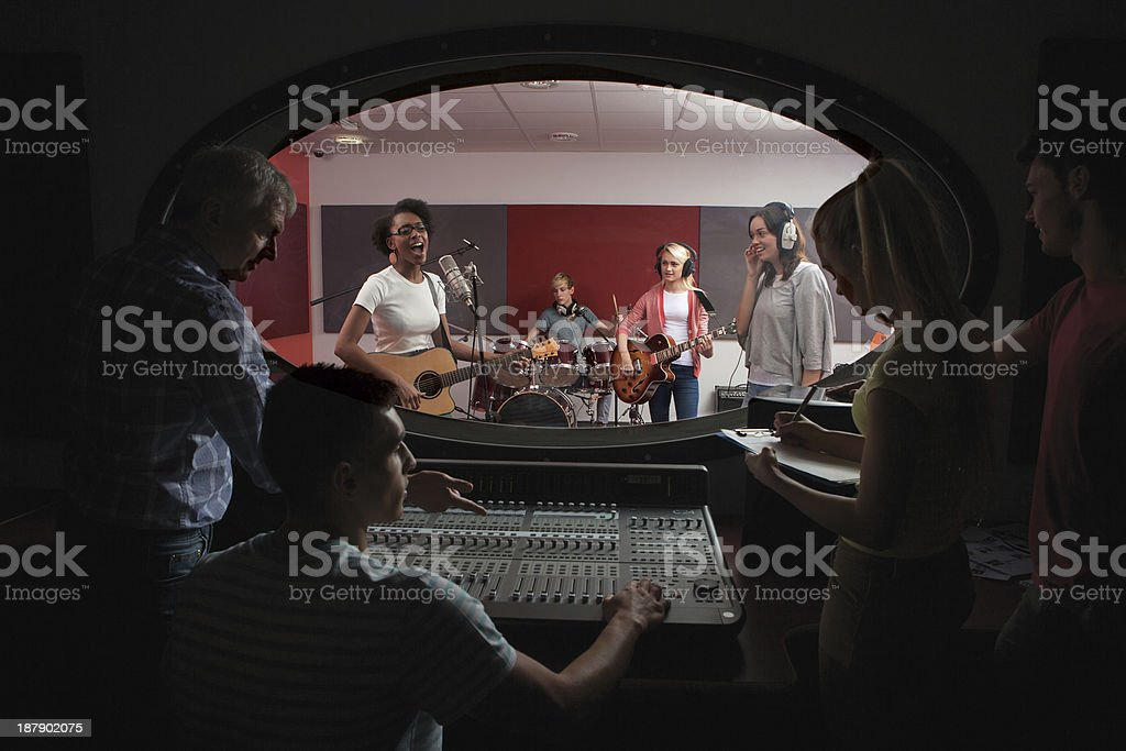 Band with lead singer in recording studio stock photo