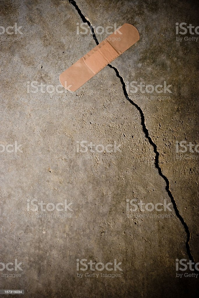 Bandage holding together a crack in the concrete stock photo