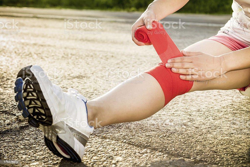 Bandaging knee closeup - sports injury stock photo