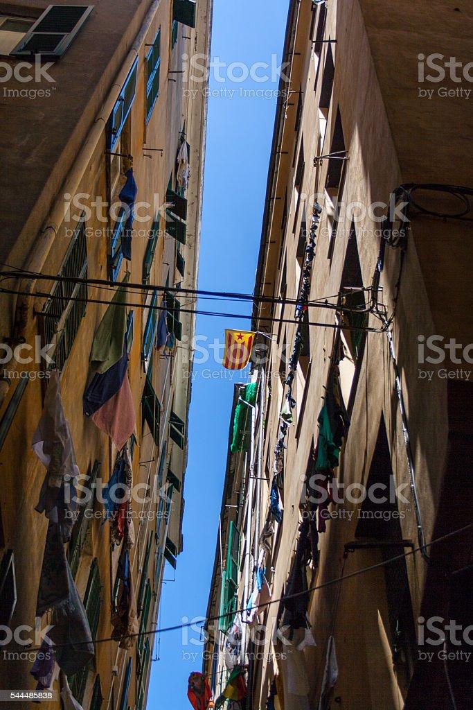 Bandiera estelada vermelia flag between two buildings in Genova, Italy. stock photo