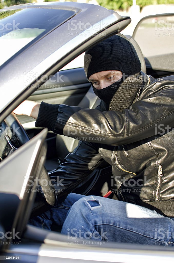 Bandit in mask stealing a car. royalty-free stock photo