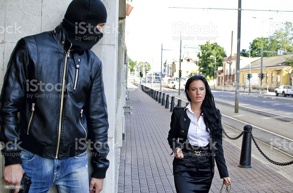 Bandit in mask with gun waiting for victim royalty-free stock photo