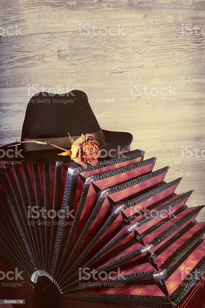 Bandoneon on wood with a male black hat stock photo