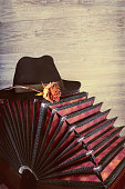 Bandoneon on wood with a male black hat