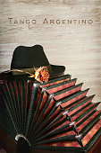 Bandoneon on wooden background, text 'Tango Argentino'
