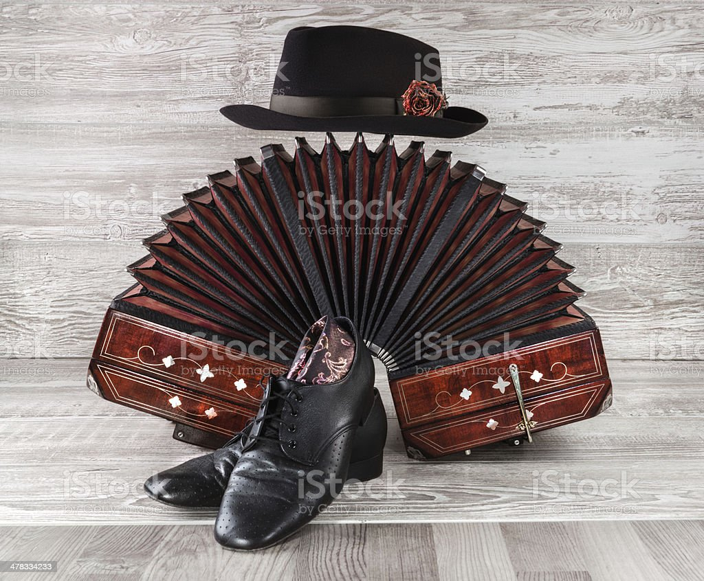 Bandoneon, tango dance shoes and male hat stock photo