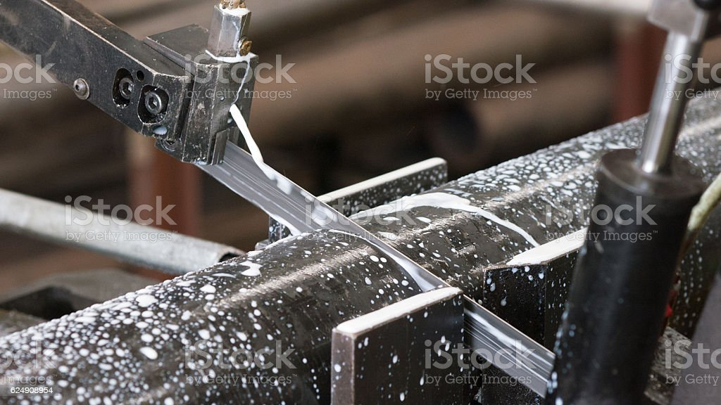 Bandsaw cutting a steel pipe stock photo