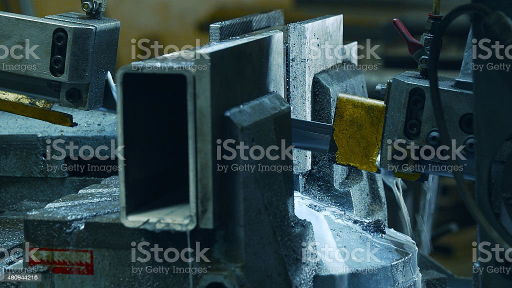 Bandsaw cutting iron beam at factory stock photo