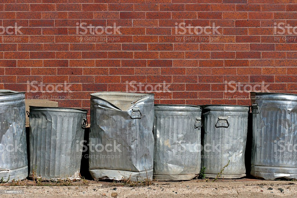 Banged up metal trash cans in an urban setting stock photo