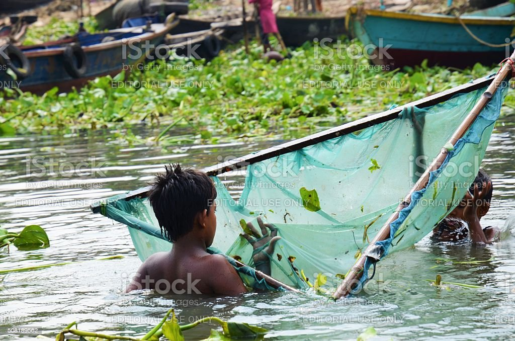 Bangladeshi children in the river with fishing net stock photo