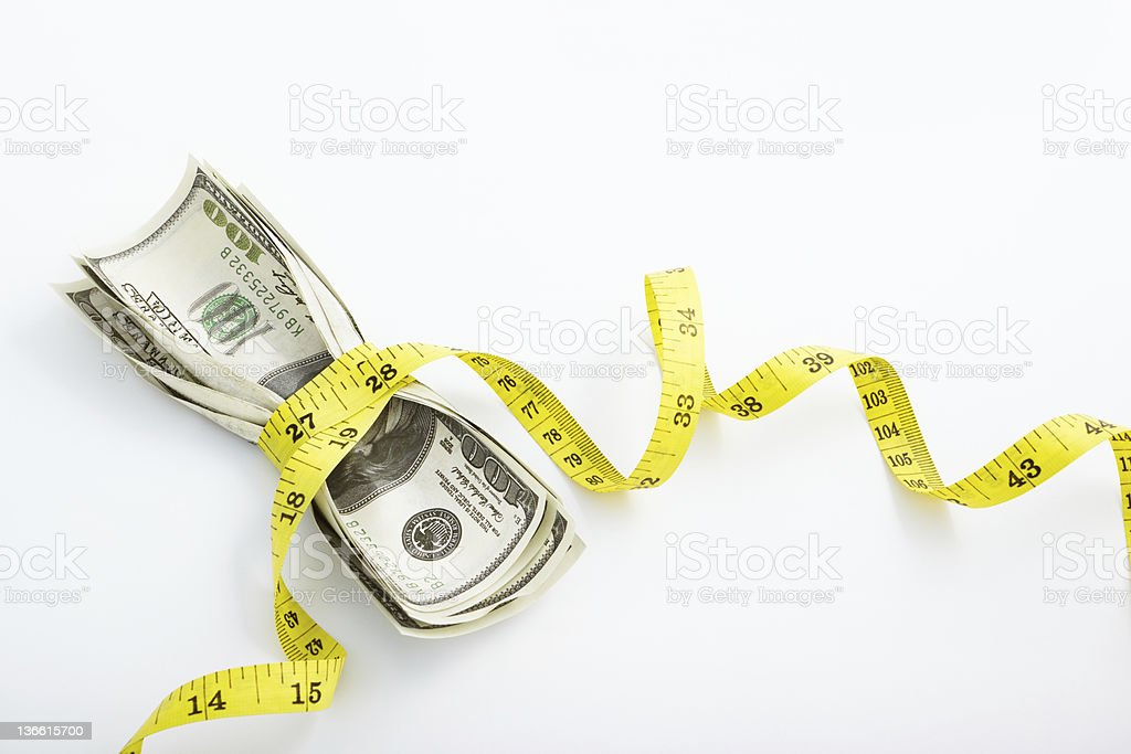 Bank notes wrapped in yellow measuring tape stock photo