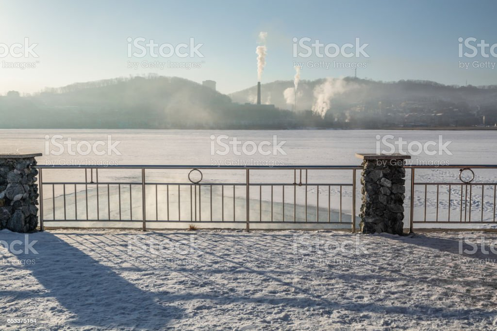 Bank of frozen lake and big steamshop's pipe on background. stock photo