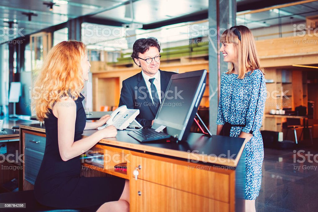 Bank receptionist helping customers stock photo