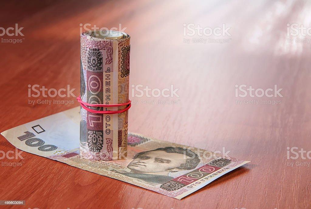 Bank Roll of Ukrainian hryvnia on the table stock photo