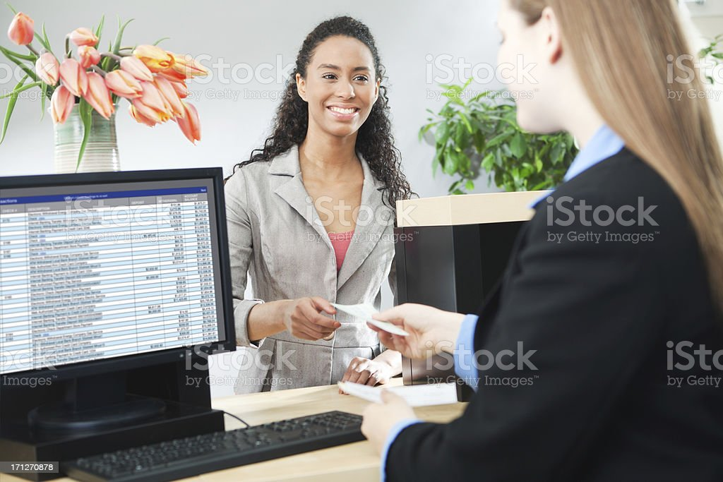 Bank Teller Servicing Banking Customer Transaction Over Retail Counter stock photo