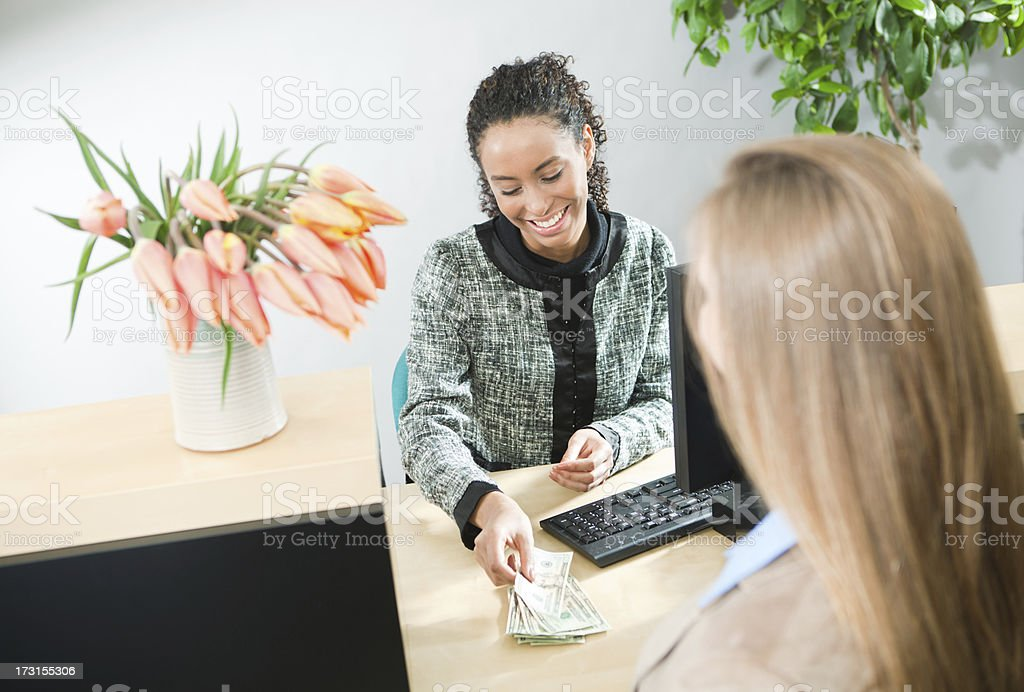 Bank Teller Serving Customer, Currency Transaction at Retail Banking Counter stock photo