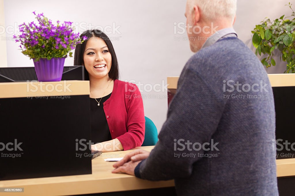 Bank Teller Serving Customer Over Retail Banking Service Counter stock photo