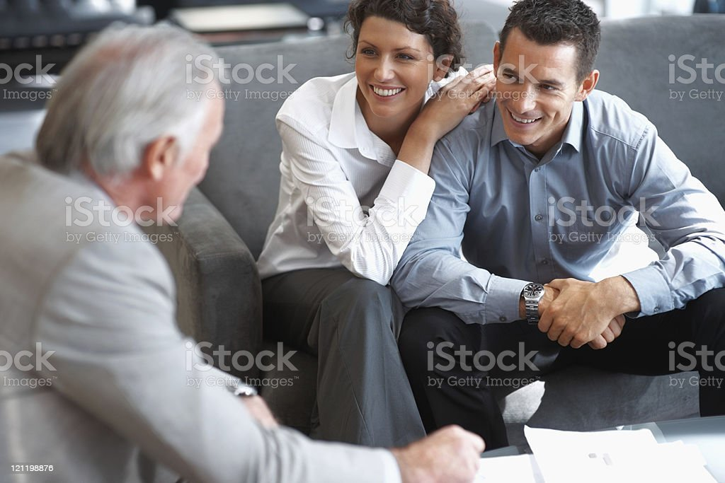 Banking agent explaining an investment scheme to a couple royalty-free stock photo