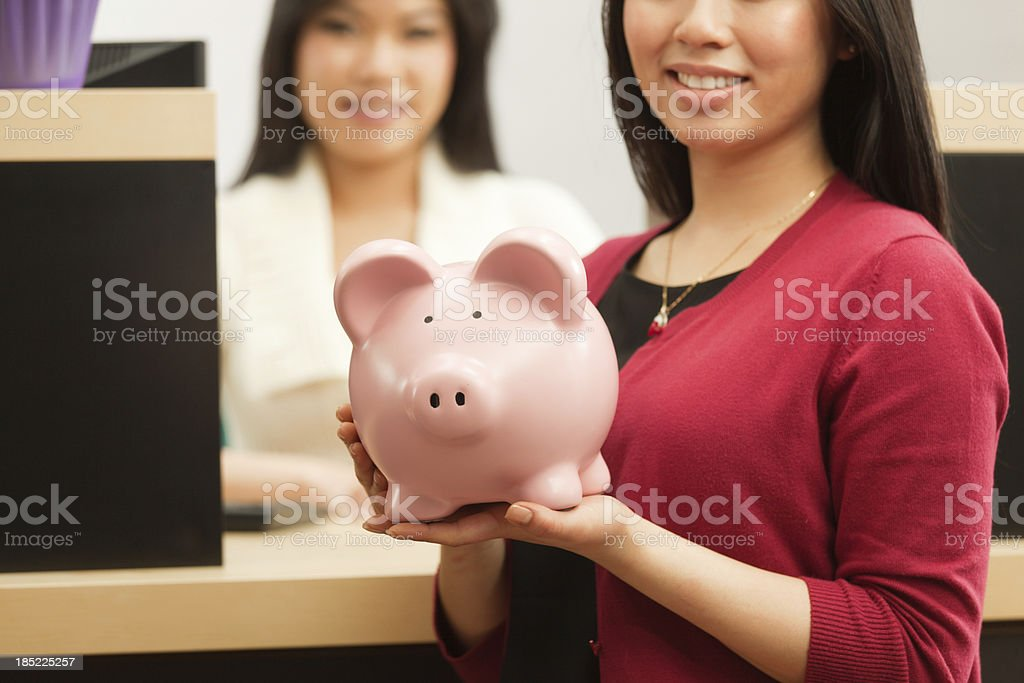 A banking customer with her piggy bank saving in front of an Asian...