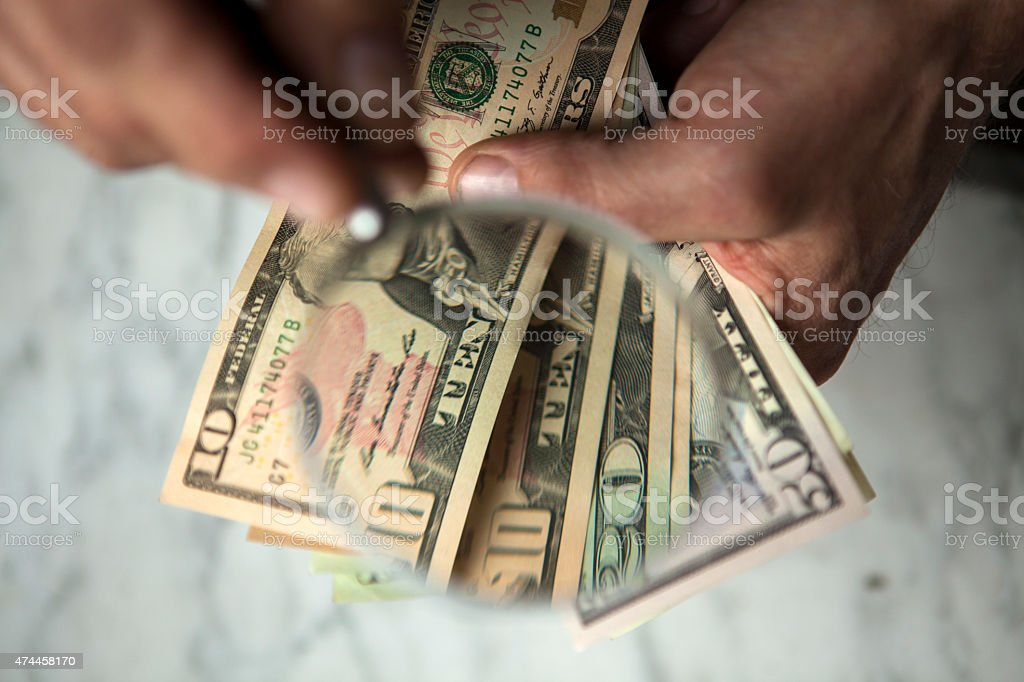 Banknotes and magnifying glass stock photo