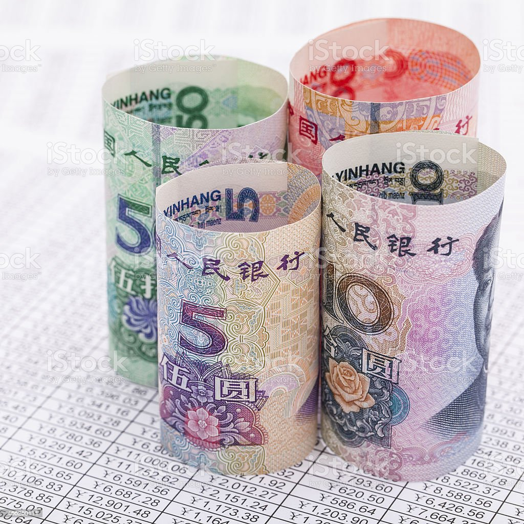 RMB banknotes rolled up on financial reports stock photo
