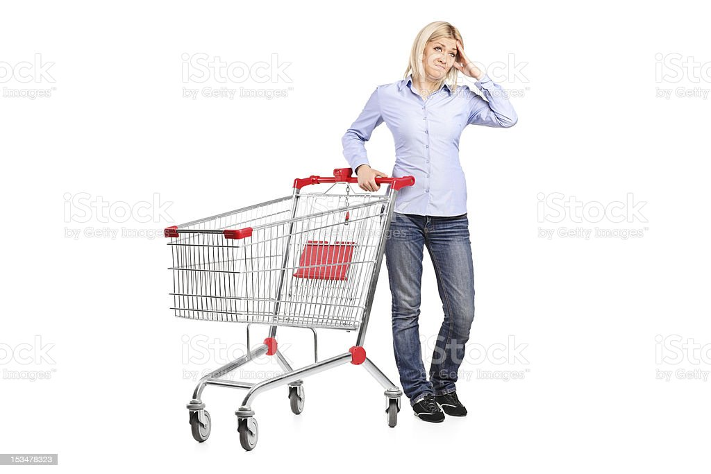 Bankrupt woman posing next to an empty shopping cart royalty-free stock photo