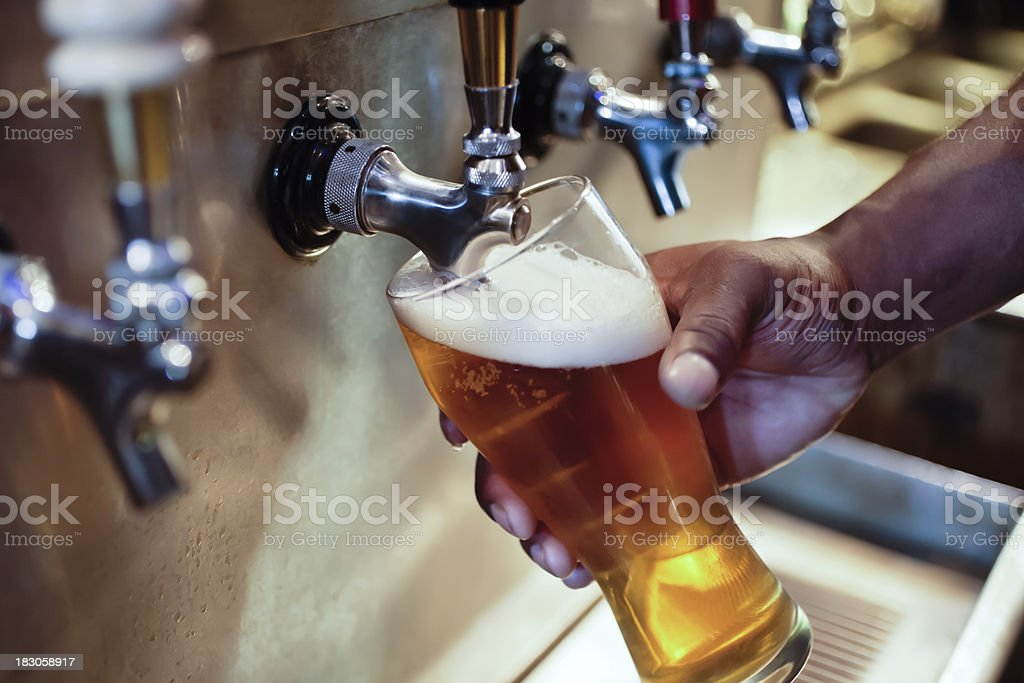 Bar Beer Tap with African American Person's Hand Filling Glass royalty-free stock photo