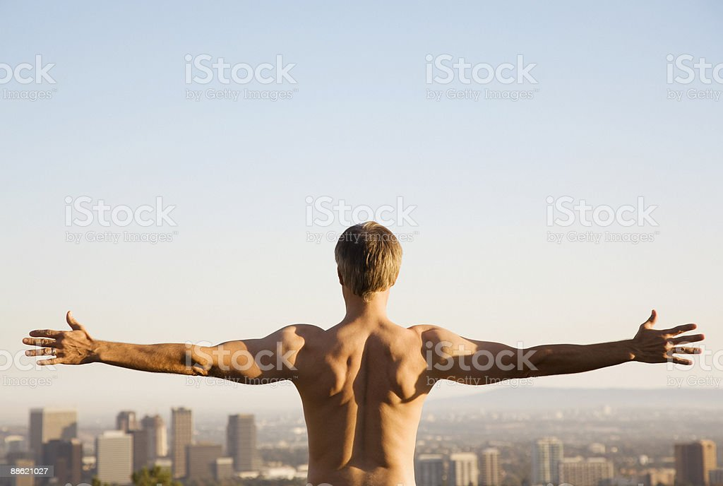 Bar chested man stretching on balcony overlooking city royalty-free stock photo