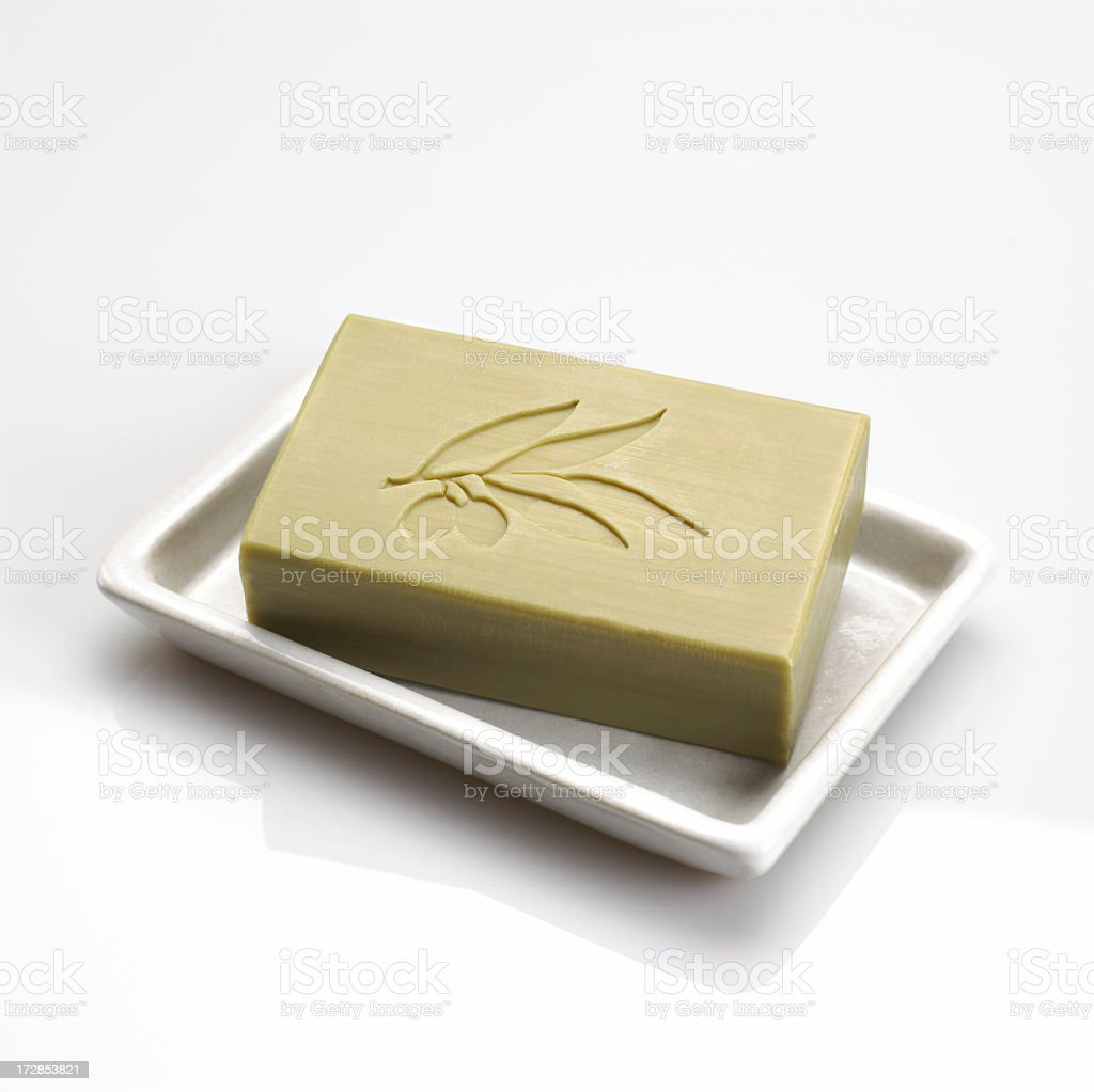 Bar of olive soap in a white dish isolated on white stock photo