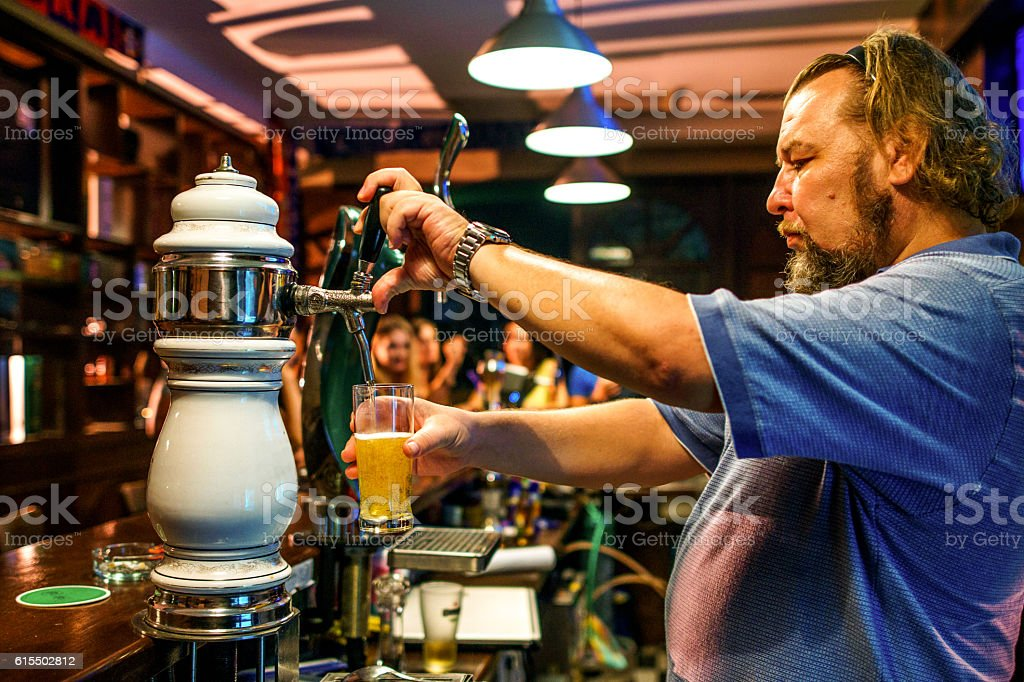 Bar owner pouring beer stock photo
