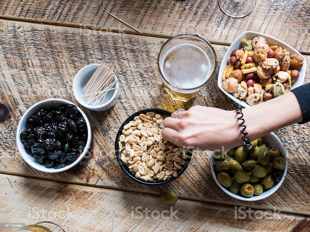 Bar snacks and a pint of beer on wooden table stock photo