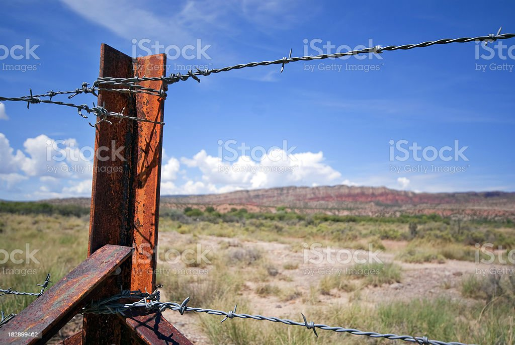 barb wire fence post desert landscape stock photo