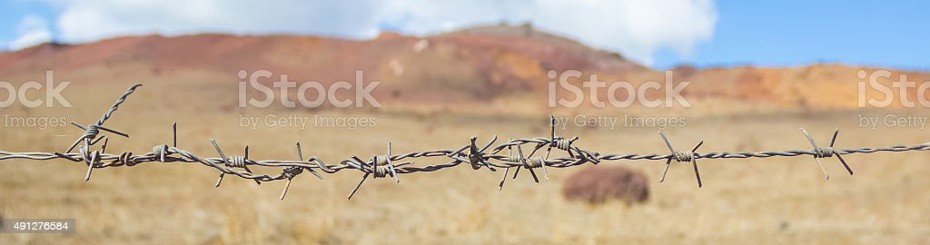 barb wire on a desert landscape stock photo